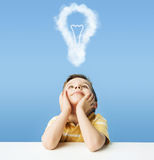 Little boy dreaming about a light bulb Stock Images