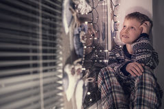 Little boy dreaming about Santa presents. Sitting jn the decorated window Stock Image