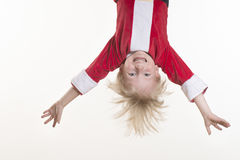 Little boy dressed as Santa Claus is hanging upside down Stock Photo