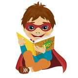 Little boy dressed as a superhero reading a comic book Stock Images
