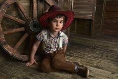Little boy dressed in cowboy sitting Stock Photos