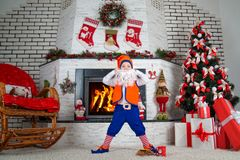 A little boy dressed in a New Year`s costume of an elf.The Christmas interior.Merry Christmas and Happy Holidays! royalty free stock image
