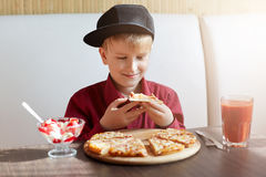 A little boy dressed in red shirt and modern cap siting in restaurant at table tasting delisious pizza and ice-cream drinking toma royalty free stock images