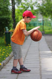 Little boy dribbling basketball sideview Royalty Free Stock Photo