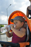 Little boy drink water sits in the stroller Royalty Free Stock Photos