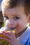 Little boy drinking 02. Beautiful Little boy with big eyes drinking his apple juice Stock Photos