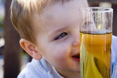 Little boy drinking. Beautiful Little boy with big eyes happy with his apple juice Royalty Free Stock Image