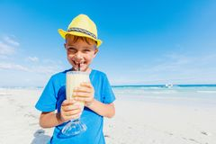 Little boy drinking cocktail on tropical beach Royalty Free Stock Photos