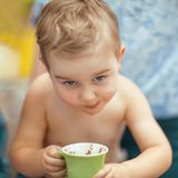 Little boy is drinking a cocoa with a mischievous expression. Sunny, summer, family mood Royalty Free Stock Image