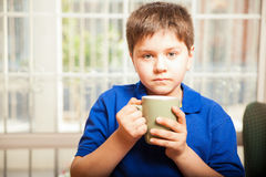 Little boy drinking coffee Stock Images