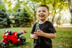 Free Little Boy Drinking Cola Standing In Front Of Red Toy Motorcycle In Summer Park Royalty Free Stock Photos - 182763308