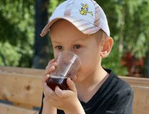 Little boy drinking cold beverage. From a plastic cup  in summer Stock Photo