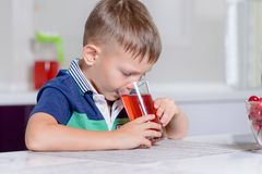 Little boy drinking fruit juice in a kitchen Royalty Free Stock Photography