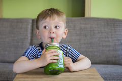 Little boy drinking a green smoothie Royalty Free Stock Photo