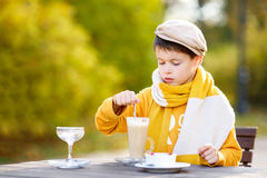 Little boy drinking hot chocolate in cafe royalty free stock images