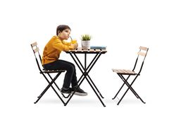 Little boy drinking juice and sitting alone at a table stock photos