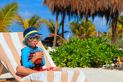 Little boy drinking juice on tropical beach royalty free stock photos
