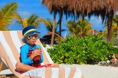 Little boy drinking juice on tropical beach Royalty Free Stock Photos
