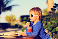 Little boy drinking juice on tropical beach Stock Photography