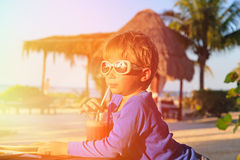 Little boy drinking juice on tropical beach Stock Image