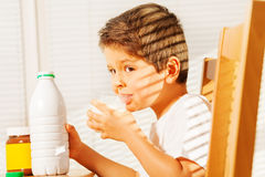 Little boy drinking milk during breakfast Stock Photography