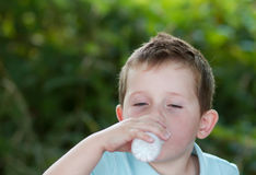 Little boy drinking milk from a small white bottle Stock Photo