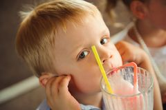 Little boy drinking milkshakes in a cafe outdoors. Little boy drinking milkshakes in a cafe outdoors stock photography