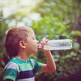 Little boy drinking mineral water from the plastic bottle on out. Door. Toning image Stock Photography