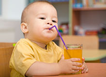 Little boy is drinking orange juice Royalty Free Stock Photography