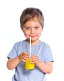 Little boy drinking orange juice Stock Images