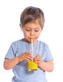 Little boy drinking orange juice Stock Photos