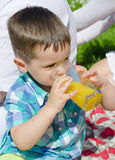 Little boy drinking orange juice Stock Photo
