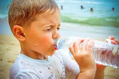 Little boy drinking water on the beach after hard Royalty Free Stock Photo