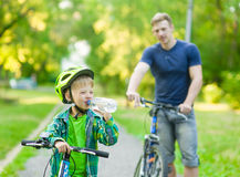 Little boy drinking water by the bike stock photo