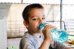 Little boy drinking water. Little brunette boy drinking water from a bottle Stock Photos