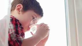 Little boy drinking water from glass, thirsty kid, closeup portrait, water for children health care. Little boy drinking water from glass, thirsty child, closeup stock video