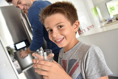 Little boy drinking water in the kitchen Stock Image