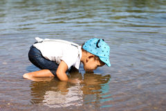 Little boy drinking water from the river Stock Photography