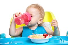 Little boy drinking water while sitting at table Stock Image