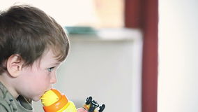 Little boy drinking water and watching TV panning, stock footage Stock Image