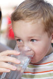 Little boy drinkng a glass of fresh water Stock Photography