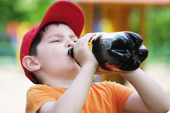 Little boy drinks from big bottle Royalty Free Stock Image