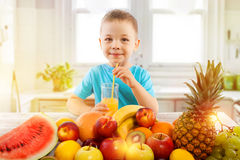 Little boy drinks fresh juice with fruits in kitchen stock image