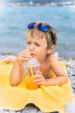 Little boy drinks juice on beach against sea Royalty Free Stock Photo