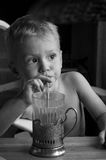 Little boy drinks through straw BW. Little boy drinks through straw. Drinking straw holding in his right hand. He looks toward. Emotion serious. old glass-holder Royalty Free Stock Photography