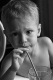 Little boy drinks through straw. Emotion serious. BW 300dpi. Little boy drinks through straw. Drinking straw holding in his right hand. He looks into the camera Royalty Free Stock Images