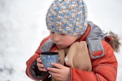 Little boy drinks tea from a cup in the frost. Stock Photography