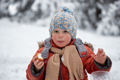 Little boy drinks tea from a cup in the frost. Royalty Free Stock Images