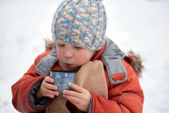 Little boy drinks tea from a cup in the frost. Royalty Free Stock Image
