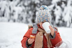 Little boy drinks tea from a cup in the frost. Stock Image